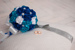 Blue wedding bouquet and wedding rings on a pillow. Wedding, bouquet, pillow, flower, ring, blue, decoration, floor, white, board, cloth, Blue wedding bouquet Royalty Free Stock Images