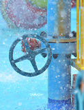 Blue wheel valve with pipe and wather flooding around. In summer Stock Photos