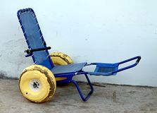 Blue wheelchair with wheels with rubber tires to go in the sea Royalty Free Stock Photography