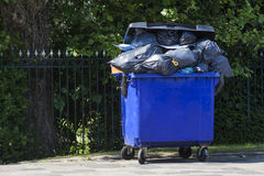 Blue wheeled garbage can. Overflowed with garbage bags in the street, in front of a garden fence Stock Image