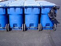 Blue wheeled trash cans and plastic garbage bag Royalty Free Stock Photo