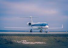 Blue and White Airplane on Concrete Ground Stock Photo