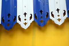Blue and white awning. On a yellow background stock image