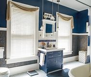 Blue & White Bathroom. Dayton, Ohio, USA - June 13, 2018: Updated blue & white bathroom of a one hundred-year-old home with antique dresser for sink vanity Stock Photos