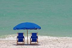 Blue and white beach. Blue beach chairs and umbrella on white sandy beacn Royalty Free Stock Photo
