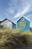 Blue & White Beach Huts. Beach huts and boats in sand dunes at Mudeford Spit on Hengistbury Head near Christchurch in Dorset Stock Image
