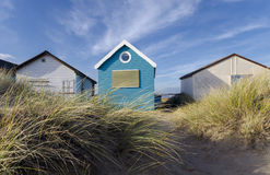 Blue & White Beach Huts. Beach huts and boats in sand dunes at Mudeford Spit on Hengistbury Head near Christchurch in Dorset Royalty Free Stock Photography