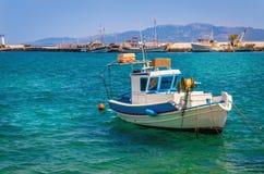 Blue-white boat floating on clear water, Greece. Small blue-white boat floating on clear water of Aegan sea on Greek coast, Kos, Greece Stock Image