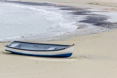 Blue and white boat on a golden sand beach. White and blue wooden boat laying on a sand and shells beach with shallow waters of the sea or ocean Stock Photos