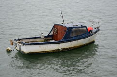 Blue and White Boat. An image of a small blue and white boat floating on the water in Devon Royalty Free Stock Photo