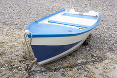 Blue and white boat on the shingle beach Royalty Free Stock Image