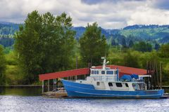 Blue and white boat sits docked along the Willamette River in Or royalty free stock photos