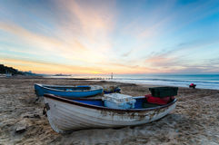 Blue & White Boats on Beach at Sunrise. Fishing boats at Durley Chine on Bournemouth beach with Bournemouth Pier in the distance Royalty Free Stock Image