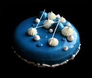 Blue and white cake with white shiny mousse cake with mirror glaze, meringues and ganache stock image