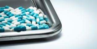 Blue-white capsule pills on stainless steel drug tray. Pharmaceutical industry. Pharmacy background. Antibiotic drug resistance. Global healthcare. Medicine royalty free stock image