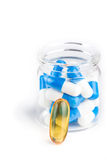 Blue white capsules in container with yellow pill Royalty Free Stock Photography
