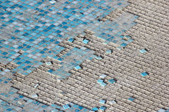 Blue and white ceramic tiles in abandoned swimming pool. Royalty Free Stock Photography