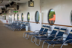 Blue and White Chaise Lounges Under Portholes. A row of blue and white chaise lounges on a cruise ship deck under large portholes royalty free stock image