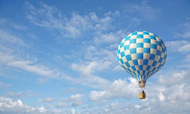 Blue-white checker hot air balloon. 3d render of blue-white hot air balloon in the blue sky Royalty Free Stock Image