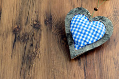 Blue white checkered heart pillow on wooden background with copy Royalty Free Stock Photos