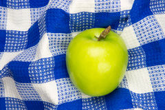Blue and white checkered table cloth with green apple Royalty Free Stock Image