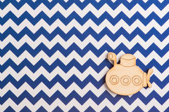 Blue white chevron desk with wooden submarine. Top view and copy space for text Stock Photography