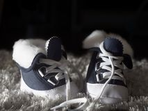 Blue and white children`s shoes on a dark background stock photography