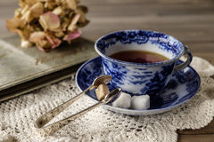 Blue and white china cup and saucer close up. Close up of antique blue and white china cup and saucer with tea on lace cloth on wooden table with out of focus royalty free stock photography