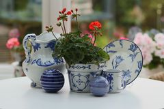 Blue and white china with red geranium still life. Blue and white china on white table with red geranium. Blurred garden background stock images