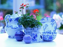 Blue and white china with red geranium still life. Blue and white china on white table with red geranium in a home conservatory. Blurred garden background royalty free stock photos