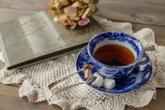 Blue and white china tea cup and saucer on lace cloth. Antique blue and white china cup and saucer with tea and sugar cubes on lace cloth on wooden table with royalty free stock photography
