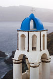 Blue and white church, Greece. Blue and white church's belltower with beautiful view of the sea at Oia village in Santorini island, Greece Royalty Free Stock Images