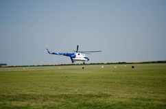 Blue-white civil helicopter soars from the airfield Royalty Free Stock Photos