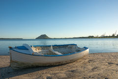Blue and white clinker boat sits on beach Stock Image