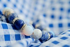 Blue and white color tone lucky fortune stone bracelet include which Lapis lazuli, Sodalite, Howlite and Moonstone on blue white b. Ackground. Amulet accessories Stock Images