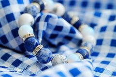 Blue and white color tone lucky fortune stone bracelet include which Lapis lazuli, Sodalite, Howlite and Moonstone on blue white b. Ackground. Amulet accessories Stock Photo