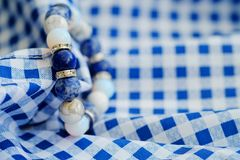 Blue and white color tone lucky fortune stone bracelet include which Lapis lazuli, Sodalite, Howlite and Moonstone on blue white b. Ackground. Amulet accessories Stock Image