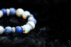 Blue and white color tone lucky fortune stone bracelet include which Lapis lazuli, Sodalite, Howlite and Moonstone on black wool b. Ackground. Amulet accessories Stock Image