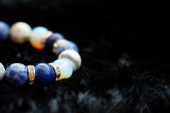 Blue and white color tone lucky fortune stone bracelet include which Lapis lazuli, Sodalite, Howlite and Moonstone on black wool b. Ackground. Amulet accessories Royalty Free Stock Images