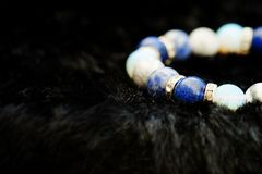 Blue and white color tone lucky fortune stone bracelet include which Lapis lazuli, Sodalite, Howlite and Moonstone on black wool b. Ackground. Amulet accessories Stock Photo