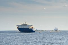 Blue and white colour project cargo ship anchors in the open sea stock images