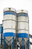 Blue and white concrete factory against white sky. Royalty Free Stock Photos