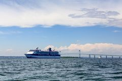 Blue and White Cruise Ship by Bridge in Newport. Blue and white cruise ship docked by bridge in Newport Rhode Island Royalty Free Stock Photography