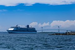 A Cruise Ship by the Newport Bridge. Blue and white cruise ship docked by bridge in Newport Rhode Island Royalty Free Stock Photography