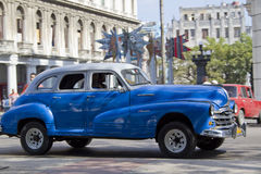 Blue and White Cuban Car. Havana, Cuba - December 25, 2010; Blue and White cuban car driving past main square Royalty Free Stock Image