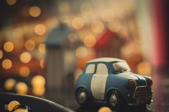 Blue and white cute cartoon car on orange bokeh background. Used car concept. Toy car model. Car toy model parked in town at night. Decoration with bokeh light stock image
