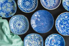 Blue and white decorative Japanese plates on black background -. Top view photo of collection of ceramic plates royalty free stock photography