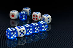 Blue and white dices on the glossy black background. Few blue and white dices on the glossy black background stock photos
