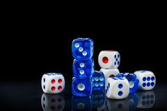 Blue and white dices on the glossy black background Stock Photos