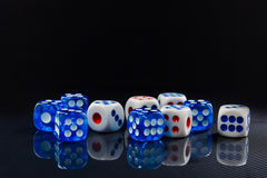 Blue and white dices on the glossy black background royalty free stock photos